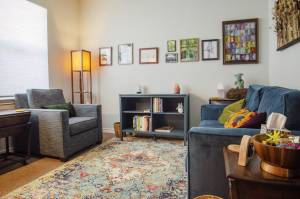 Counseling room with couch, arm chair, and book shelf with art.