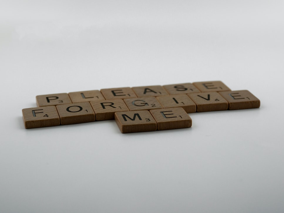 "A set of gaming set scrabble letters arranged to spell out ""please forgive me"" indicating people pleasing and remorse of trauma"