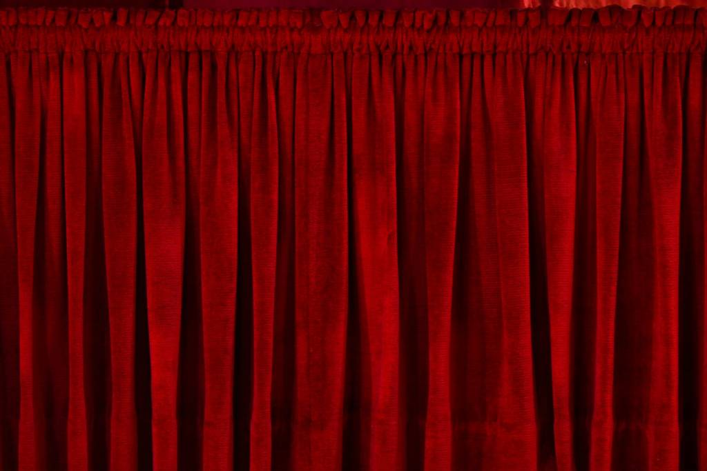 a set of closed red curtains on a stage indicating closing off